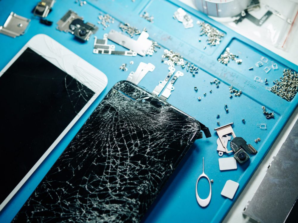 Two smartphones with broken screens and small screws on table of repairman, view from above
