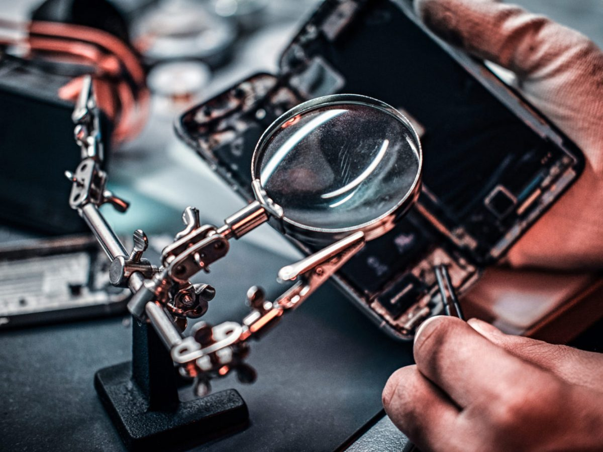 Repairman uses magnifier and tweezers to repair damaged smartphone. Close-up photo of a disassembled smartphone.