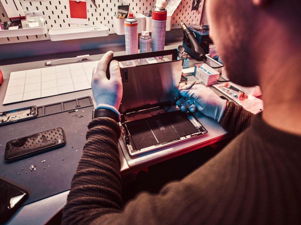 The technician repairs a broken tablet computer in a modern repair shop